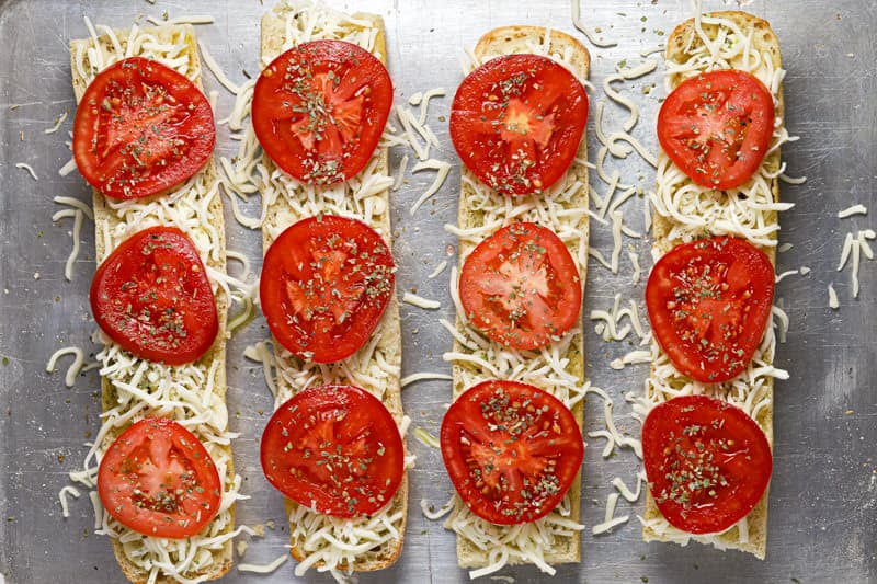Four halves of French bread topped with shredded mozzarella cheese and sliced tomatoes on a baking sheet