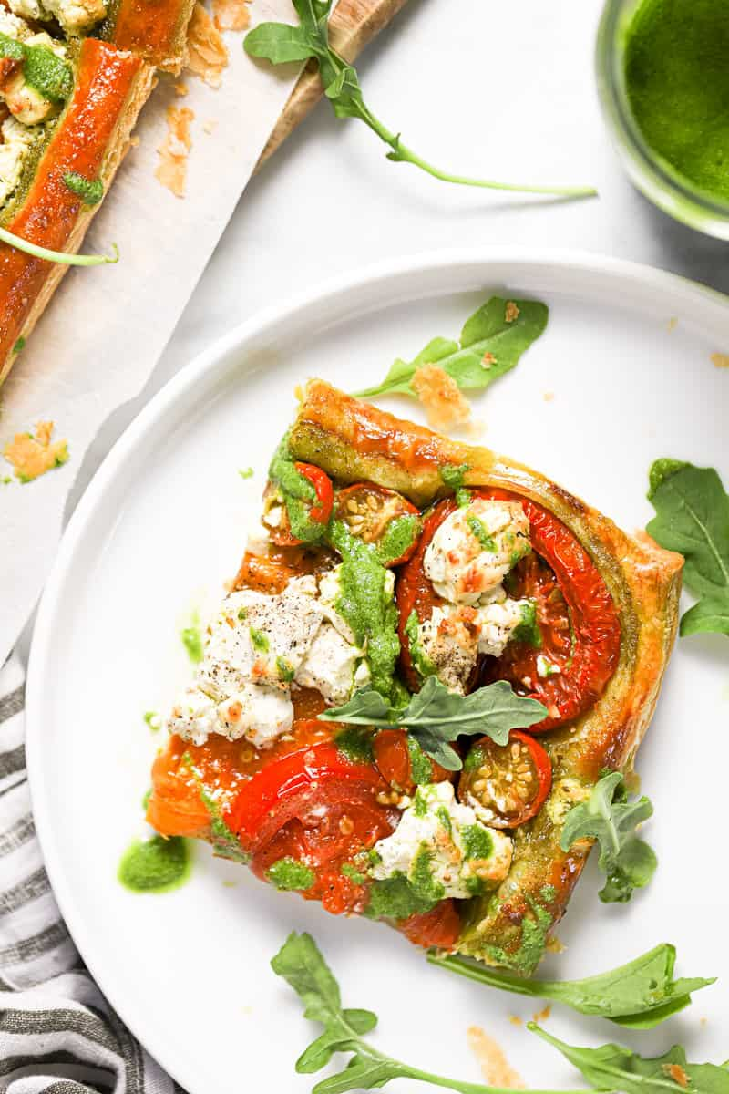 White plate with a slice of puff pastry tomato tart garnished with arugula