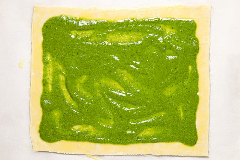 Sheet of puff pastry spread with homemade basil pesto