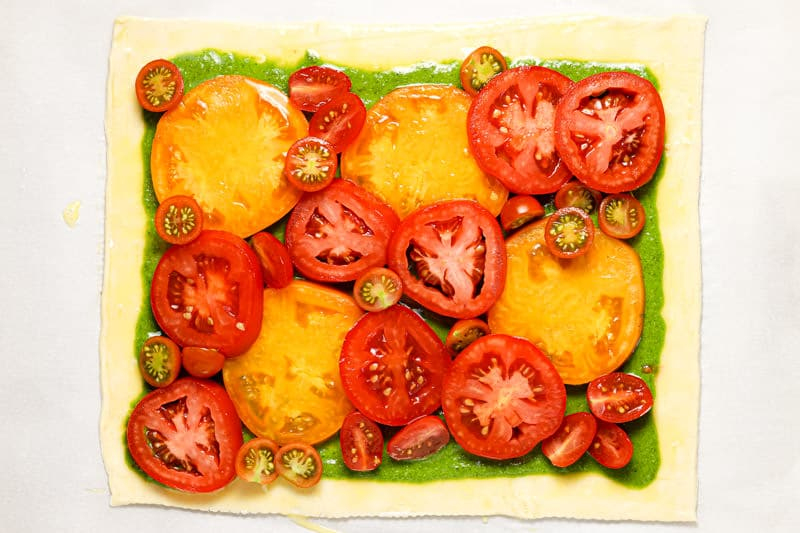 Sheet of puff pastry topped with pesto and sliced tomatoes