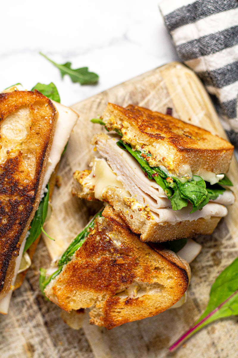 Close up shot of a sliced turkey and brie sandwich sitting on a cutting board