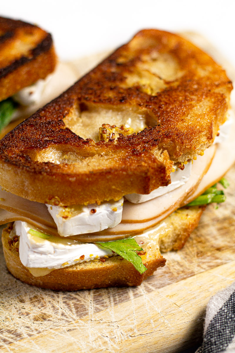 Close up shot of a grilled turkey and Brie sandwich on a cutting board