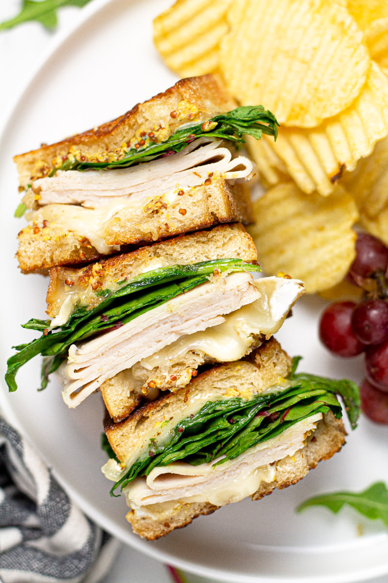 Overhead shot of a turkey and brie sandwich stacked on its side with chips
