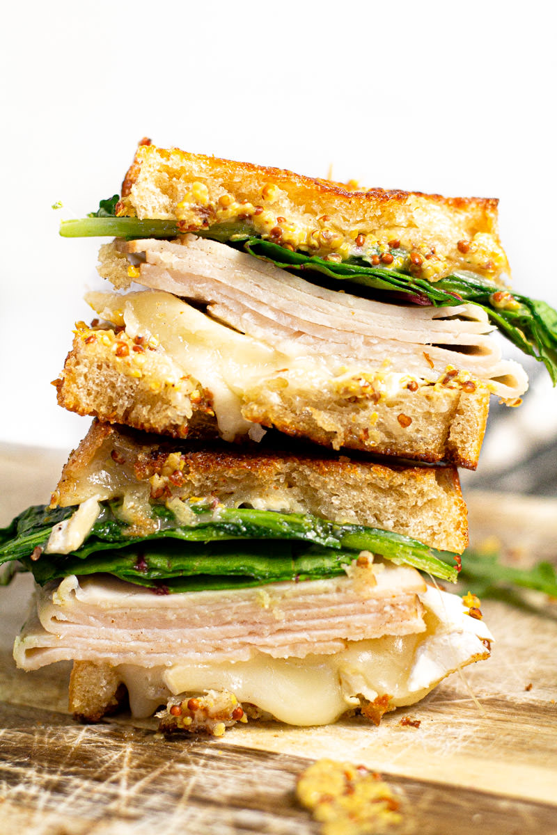 Close up shot of a turkey and brie sandwich stacked on a cutting board