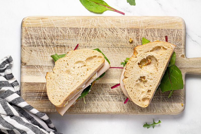 Two turkey and Brie sandwiches on a cutting board