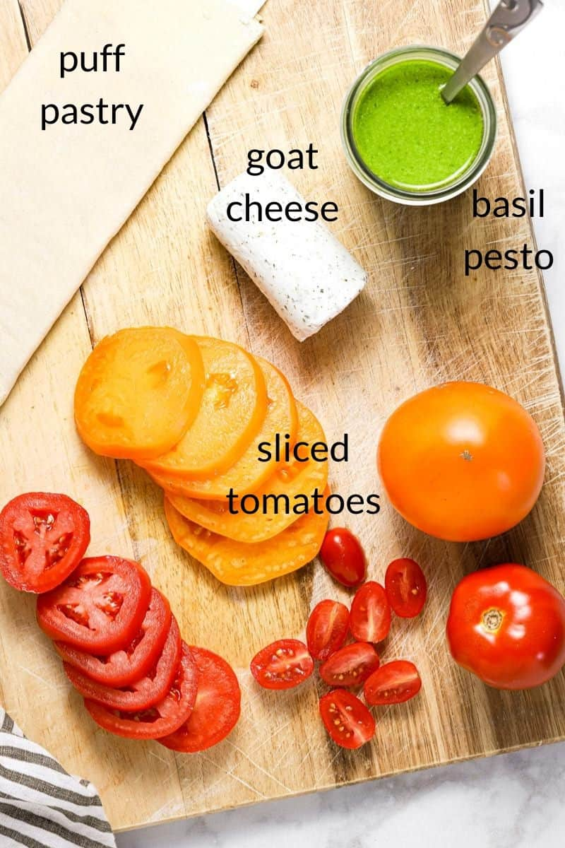 Overhead shot of a cutting board with ingredients to make a tomato tart