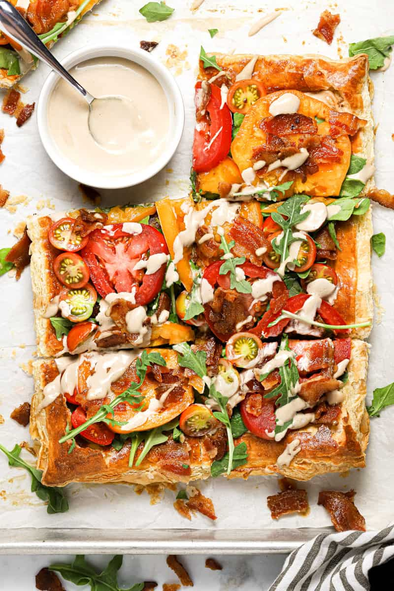 Overhead shot of a BLT puff pastry tart drizzled with balsamic mayonnaise