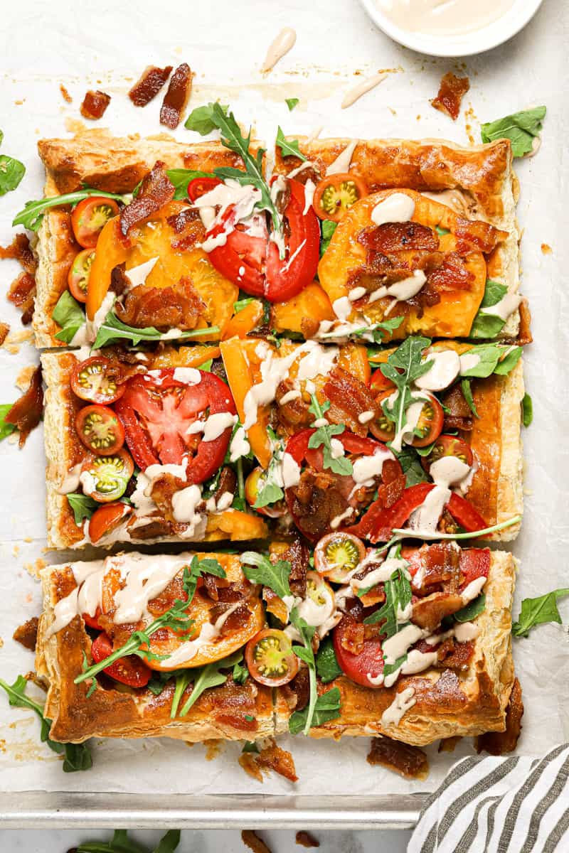 Overhead shot of a puff pastry BLT tart garnished with fresh arugula