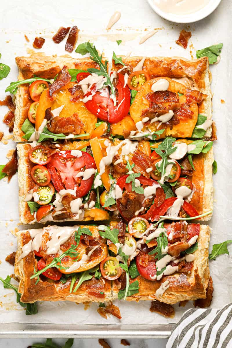 Overhead shot of a sliced BLT puff pastry tart drizzled with balsamic mayonnaise