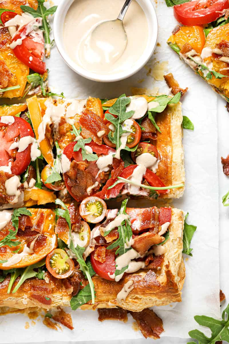Close up shot of a BLT puff pastry tart drizzled with balsamic mayonnaise