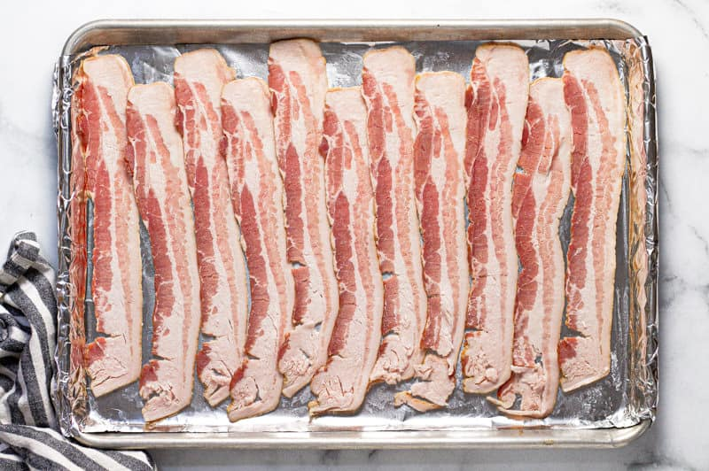 Foil lined baking sheet with raw bacon on it