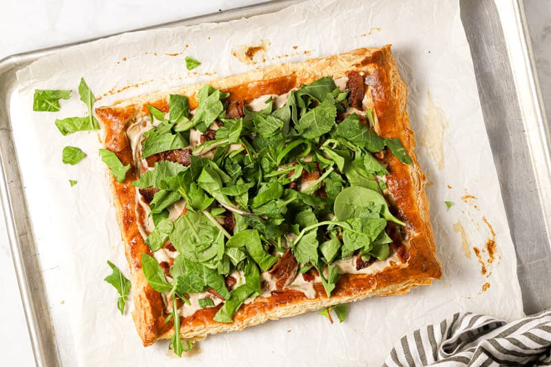 Baked puff pastry with bacon and fresh greens