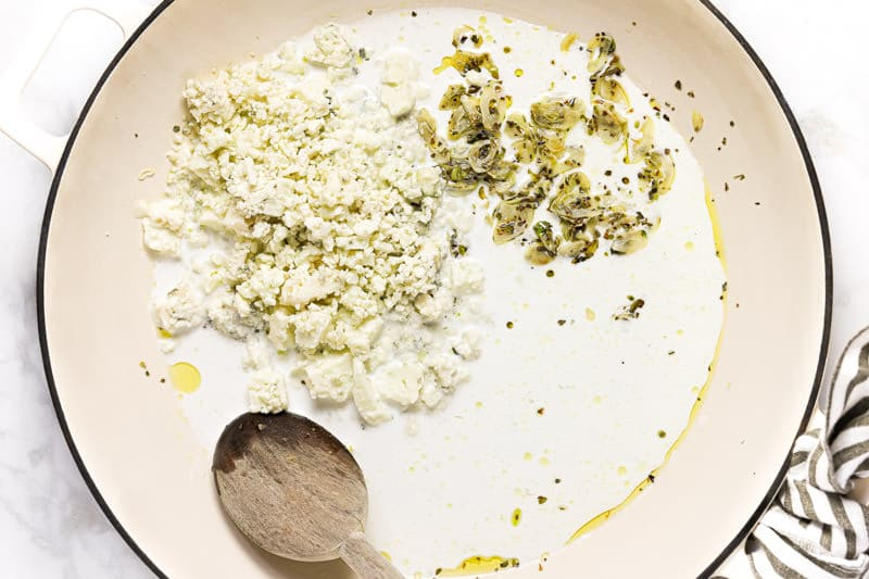 Large white pan with heavy creamy sauteed garlic and crumbled blue cheese in it
