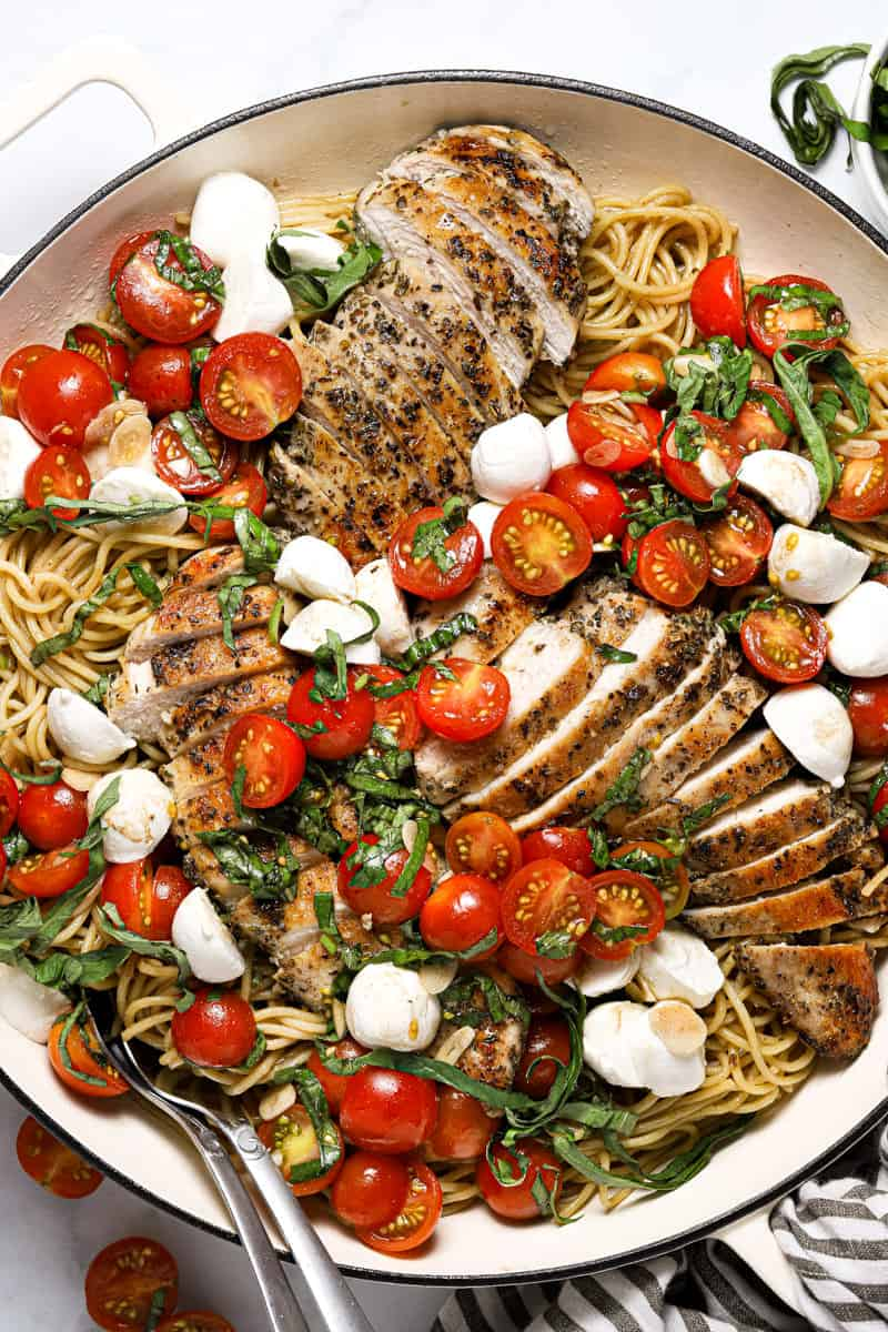 Overhead shot of a large white pan filled with spaghetti and bruschetta chicken