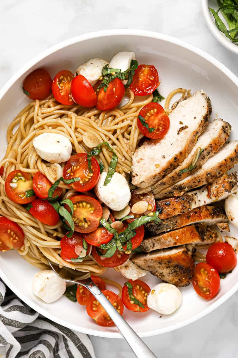 Large white plate filled with spaghetti and bruschetta chicken