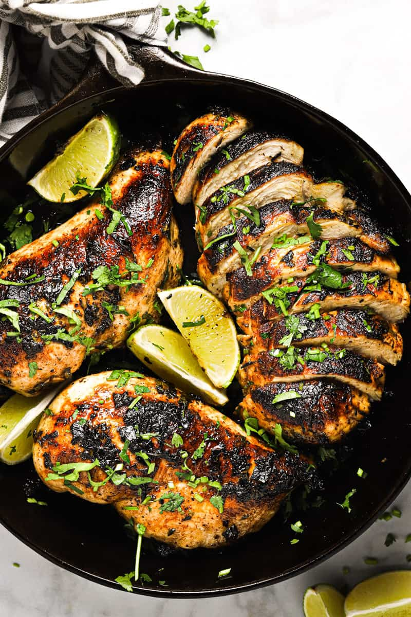 Overhead shot of a cast iron pan with golden brown sauteed cilantro lime chicken garnished with lime wedges