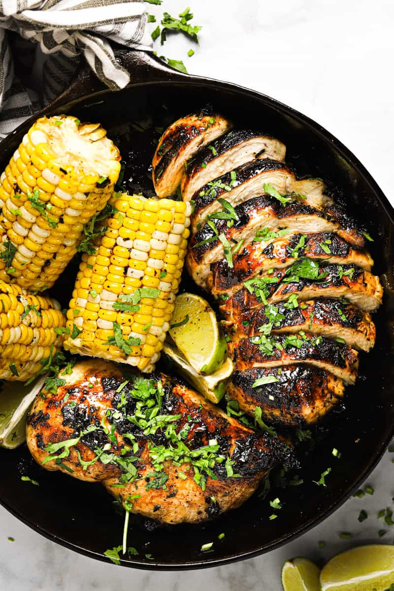 Overhead shot of a cast iron pan with golden brown sauteed cilantro lime chicken and corn on the cob