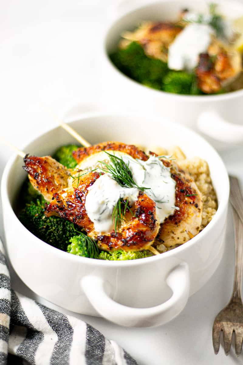 White bowl filled with Greek chicken kebabs quinoa and broccoli