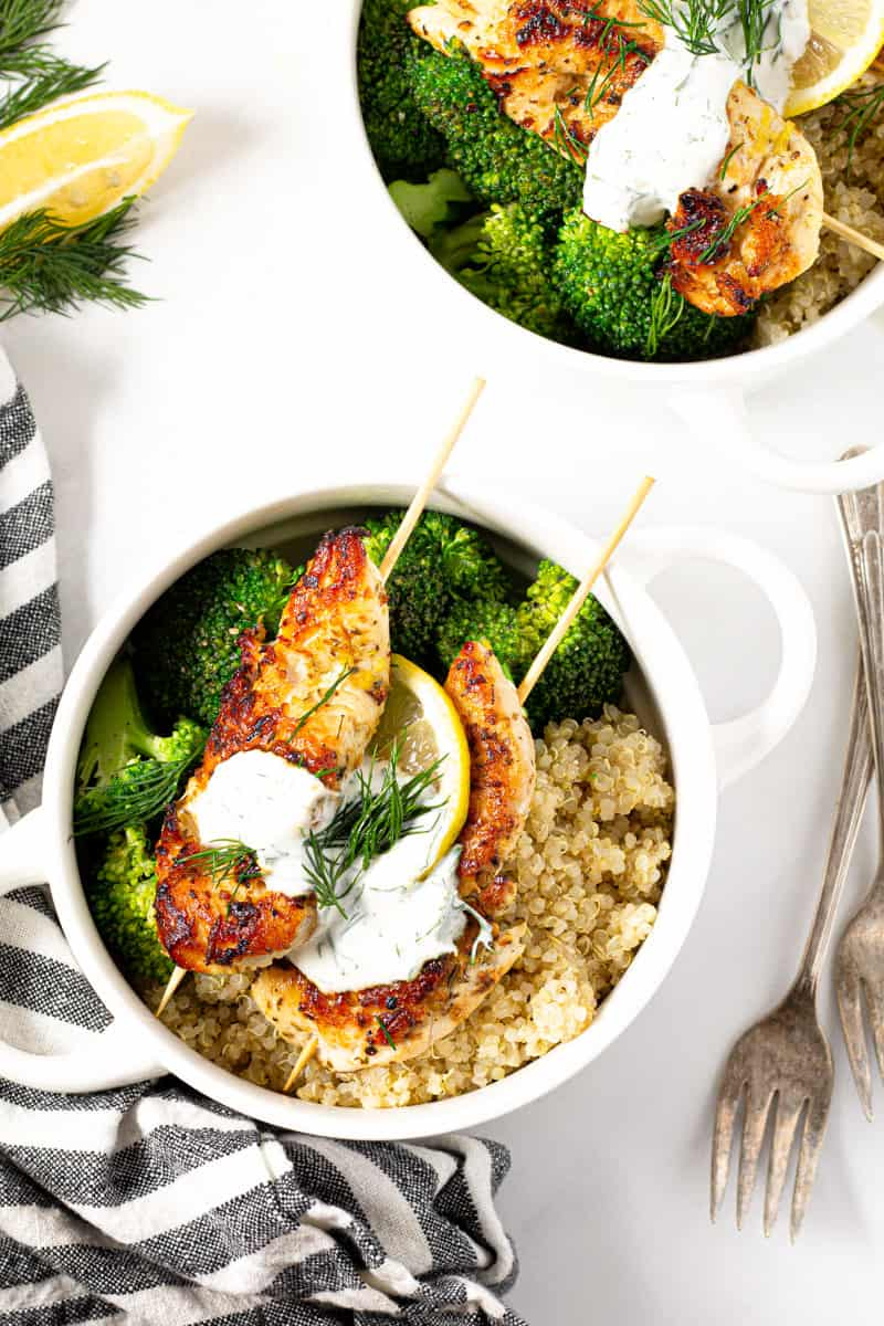 Two white bowls filled with Greek chicken kebabs quinoa and broccoli