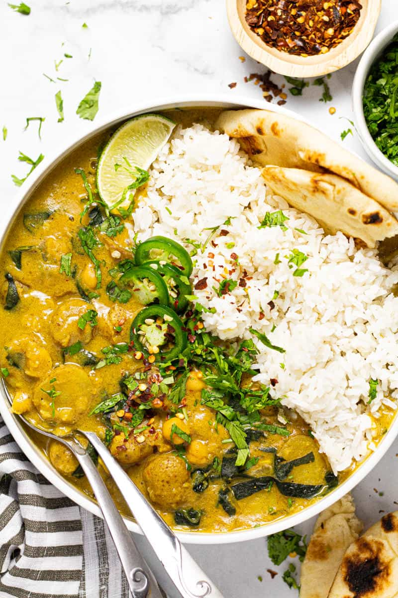 Large white bowl filled with rice and vegan curry garnished with fresh chopped cilantro