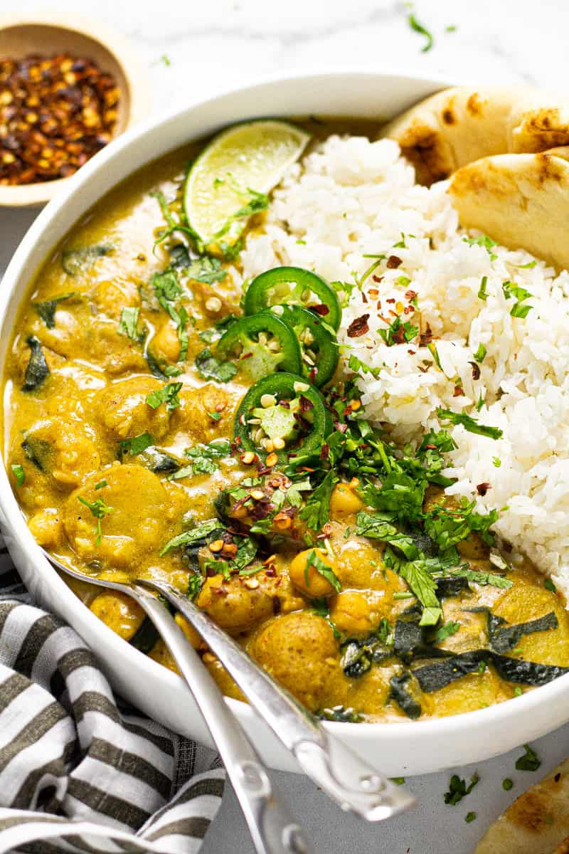 Close up shot of a large white bowl filled with rice and vegan curry garnished with fresh chopped cilantro