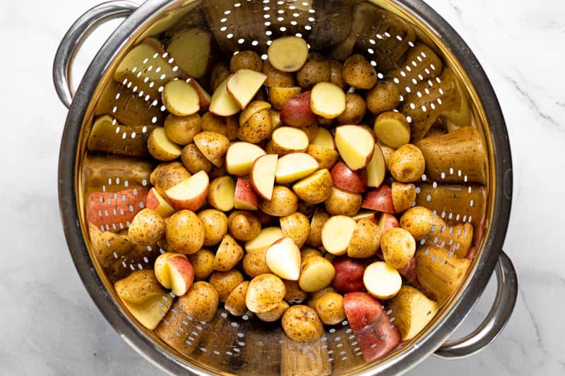 Large metal strainer filled with baby potatoes