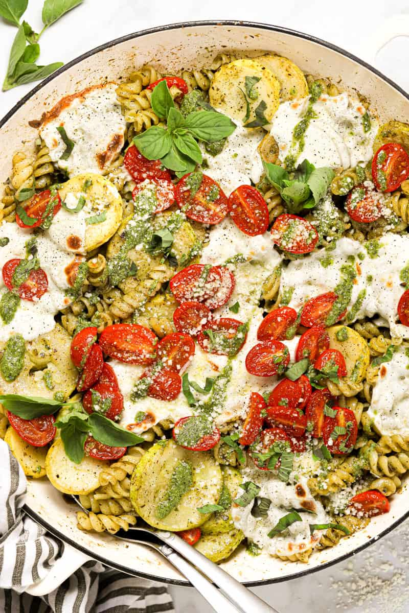 Overhead shot of a large pan of pesto pasta with tomatoes and mozzarella
