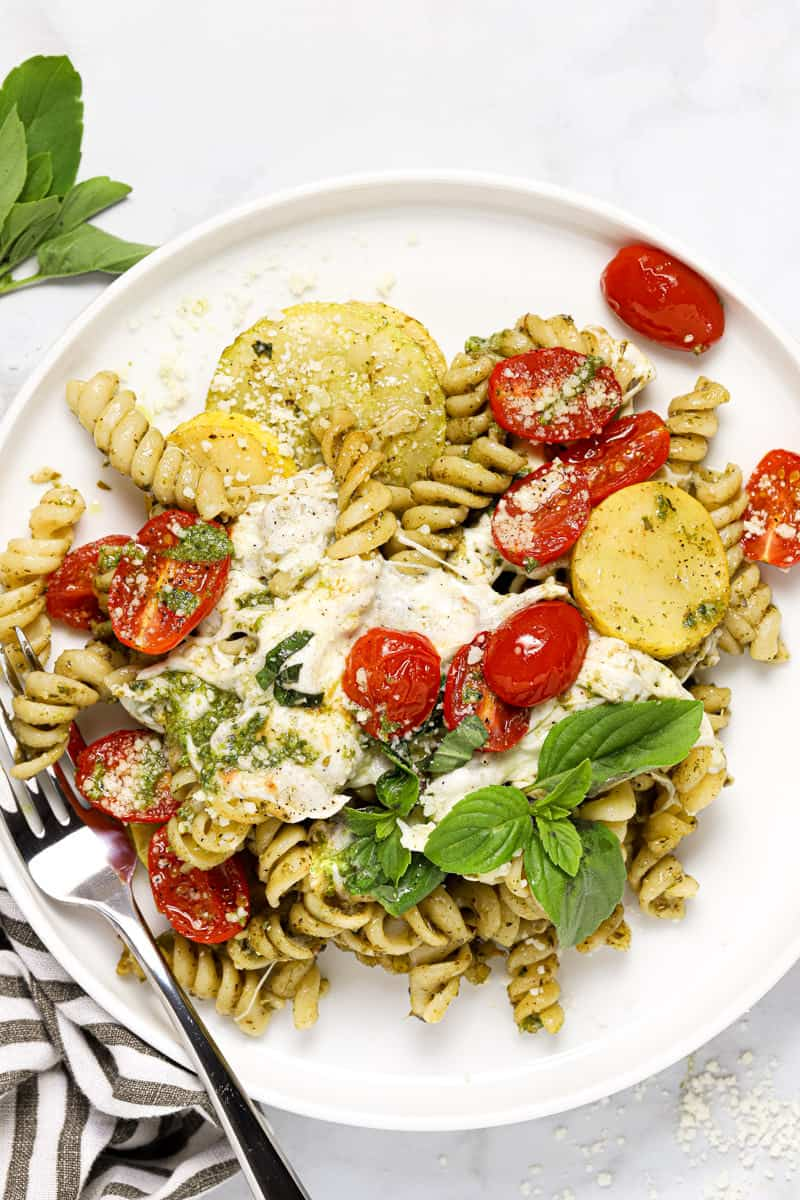 Overhead shot of a white plate of pesto pasta with tomatoes and mozzarella