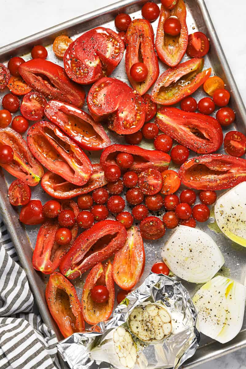 Sliced veggies on a baking sheet drizzled with olive oil and sprinkled with salt and pepper