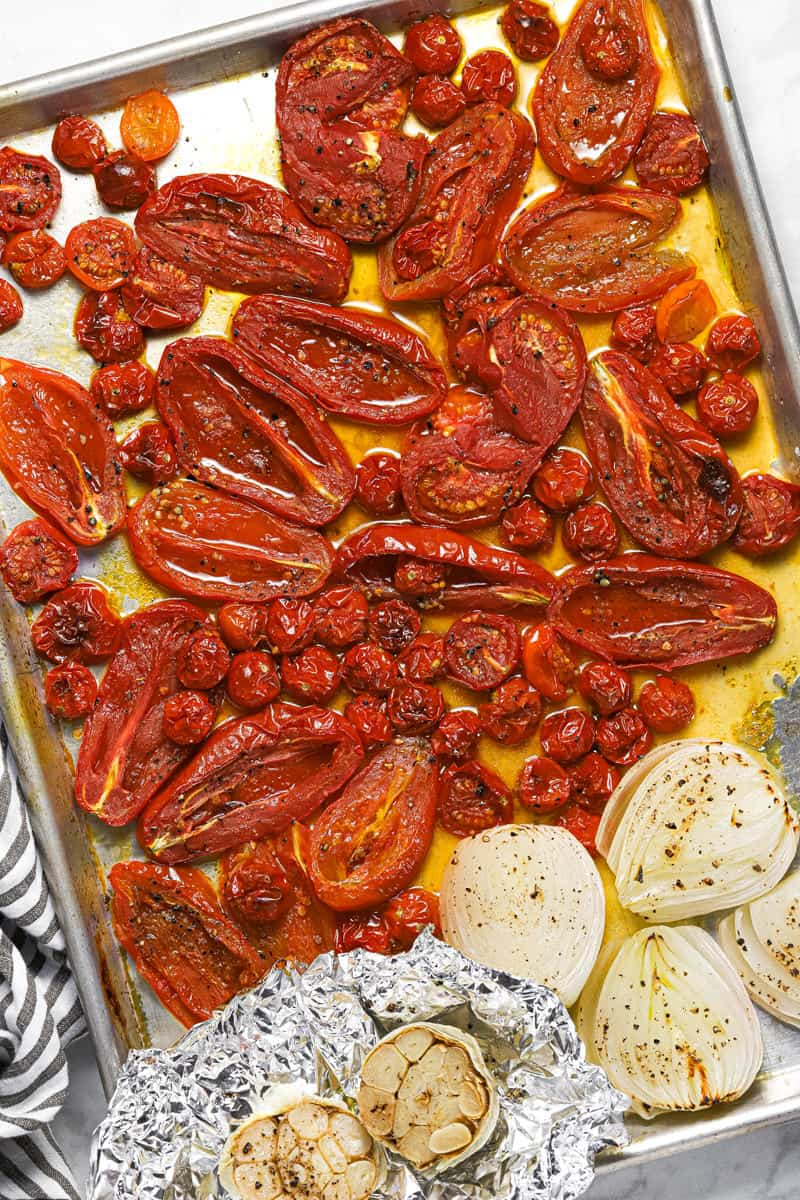 Roasted tomato onion and garlic on a metal baking sheet