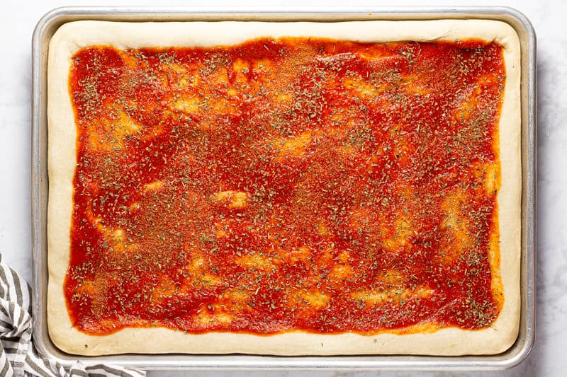 Pizza dough on a baking sheet spread with pizza sauce and seasoned with oregano