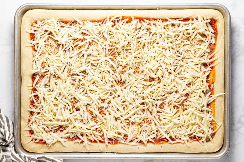 Pizza dough topped with sauce and cheese on a baking sheet