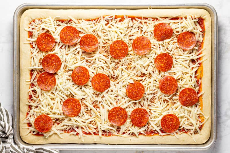 Pizza dough topped with sauce cheese and pepperoni on a baking sheet