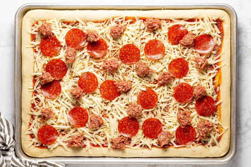 Pizza dough topped with sauce cheese pepperoni and sausage on a baking sheet