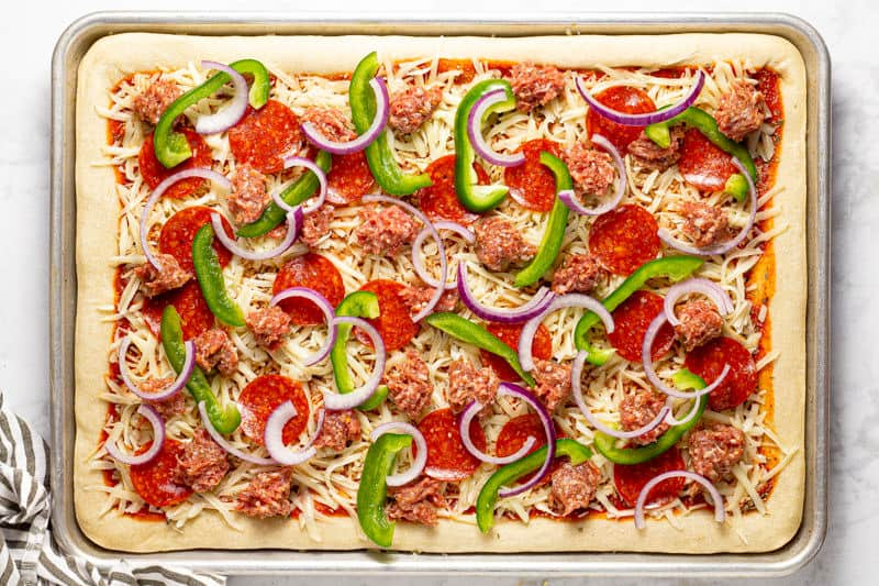 Homemade supreme pizza on a baking sheet ready to be baked