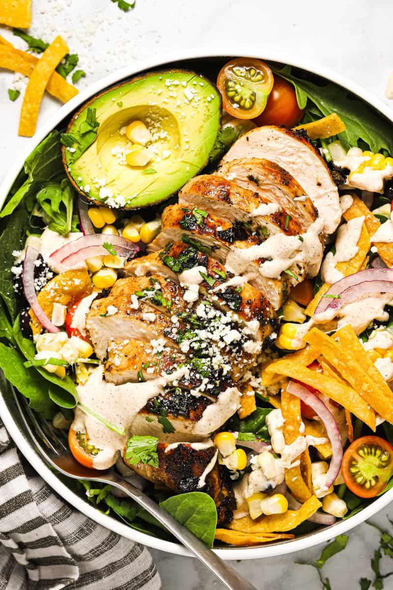 Overhead shot of a white bowl filled with southwest salad and sliced grilled chicken