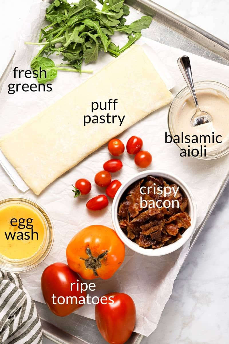 Marble counter top with ingredients to make BLT puff pastry tart