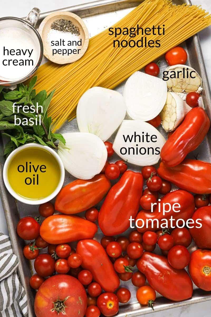 Large sheet pan with ingredients to make roasted tomato cream sauce