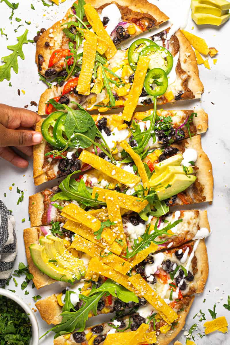 Mexican pizza flatbread on a white marble counter top with a little hand reaching for a slice