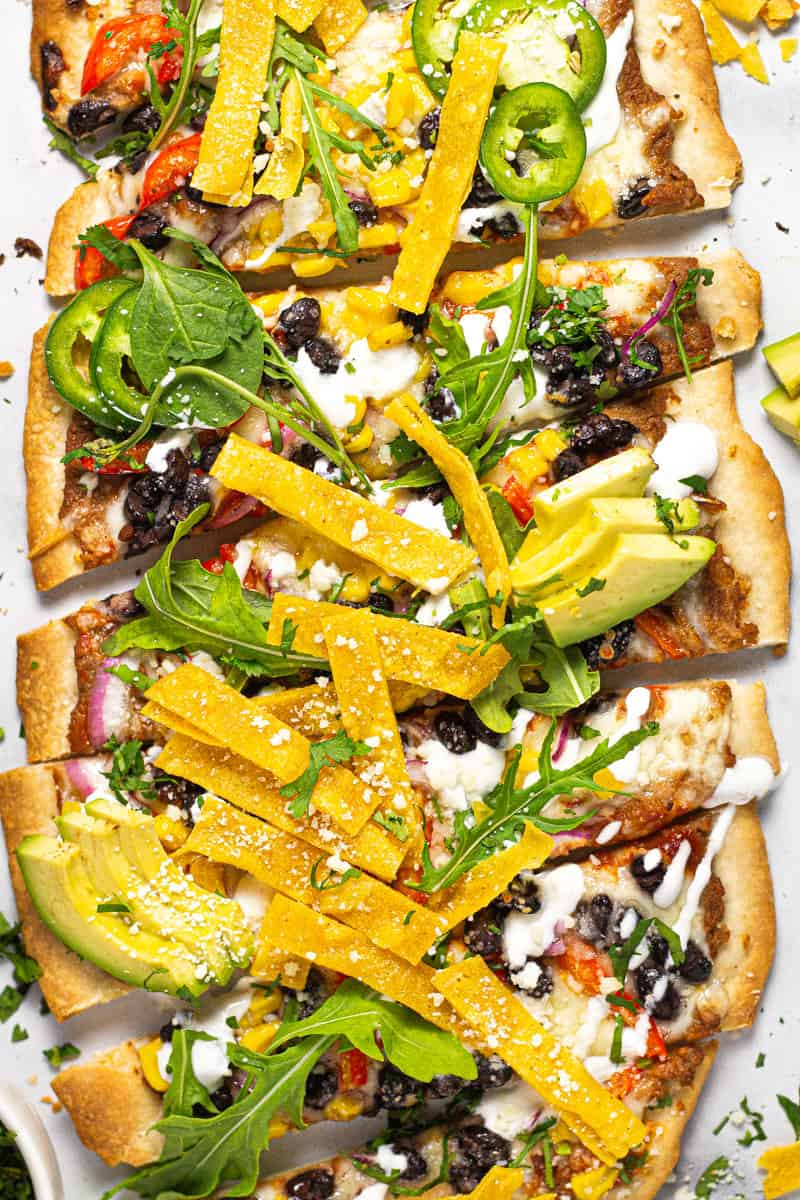 Close up of a Mexican pizza flatbread on a white marble counter top garnished with greens