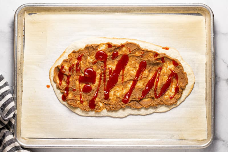 Baking sheet with flatbread crust topped with refried beans and taco sauce