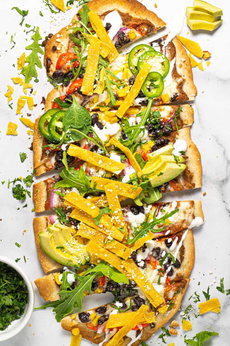 Overhead shot of a Mexican pizza flatbread on a white marble counter top garnished with greens