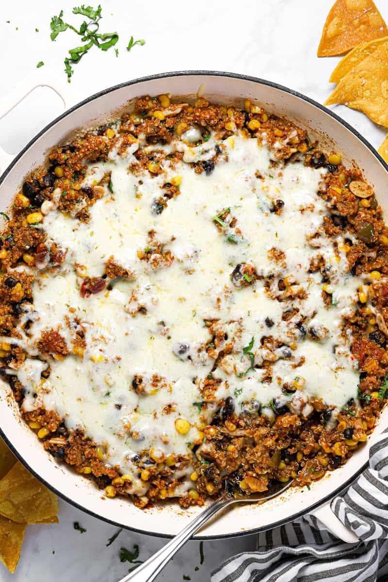 Mexican quinoa in a large white pan with melted pepper jack cheese on top