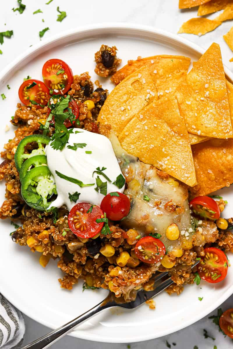 White plate with a scoop of Mexican quinoa garnished with sour cream tomatoes and chips