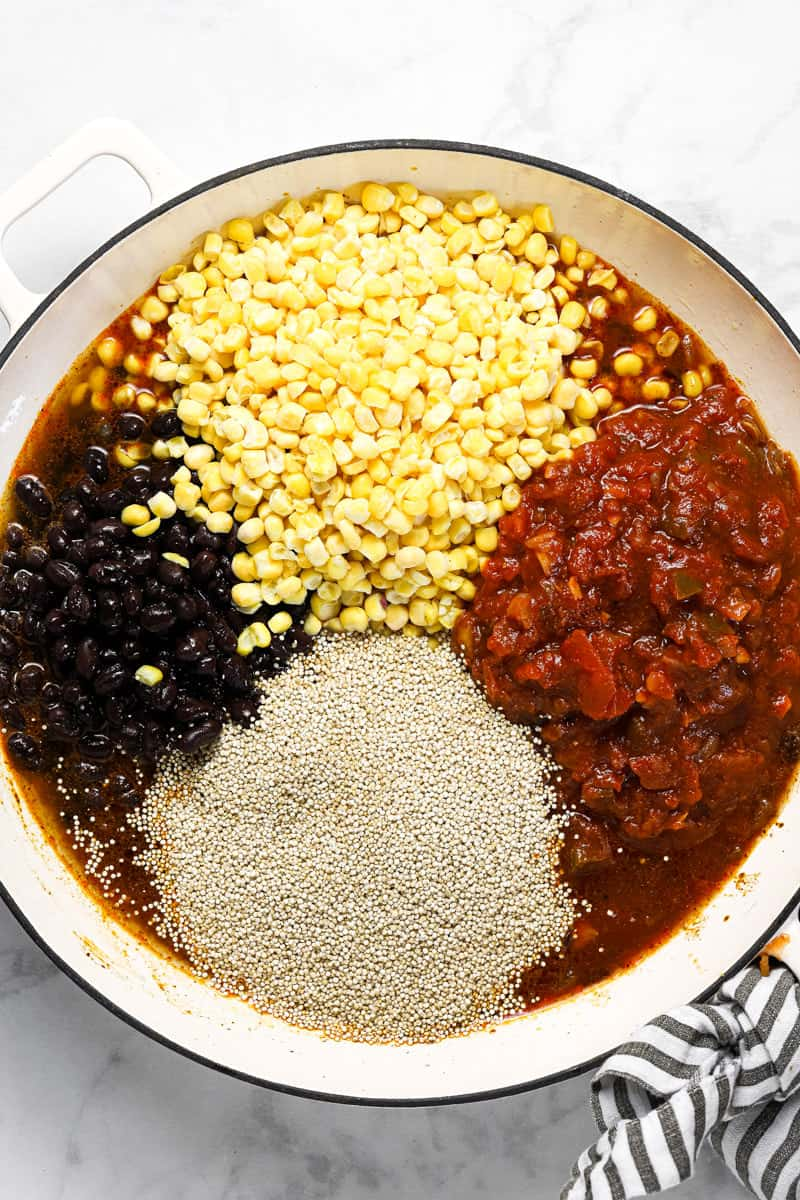 Ingredients to make Mexican quinoa in a large white pan