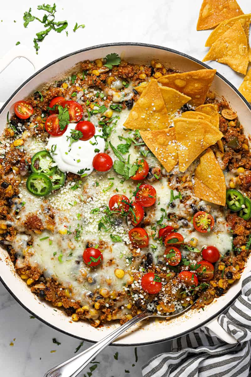 Large white pan filled with Mexican quinoa garnished with sour cream tomatoes and chips