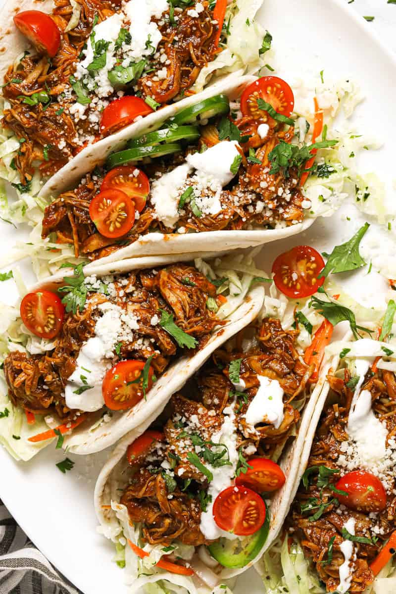 White platter filled with shredded BBQ chicken tacos garnished with fresh cilantro