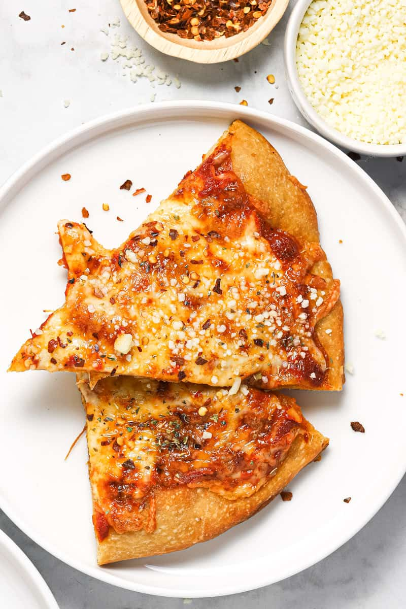 Close up shot of two slices of pizza on a white plate