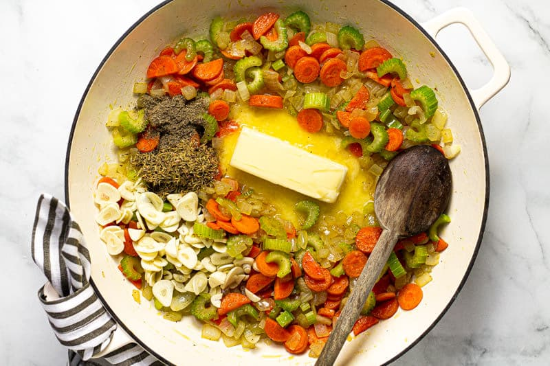 White pan filled with veggies and a stick of butter