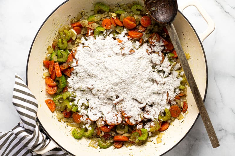 Mirepoix in a large white pan with flour added